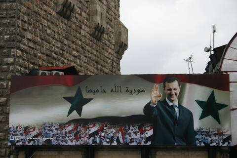 Billboard with portrait of Assad and the text Allah protects Syria on the old city wall of Damascus 2006 Photo: Bertil Videt, January 2006.