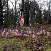 Flags on the side of Route 84 in Newtown honor the dead.