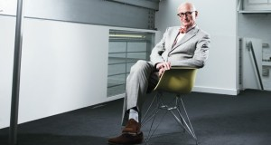 What does Wally Olin say about himself photographed in a stark room, in Corbusier glasses on an Eames chair?